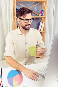 Młody pracownik siedzi w biurze z komputerem i picia herbaty