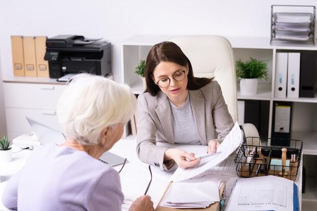 Młody pracownik socjalny w okularach mówi do starszej kobiety i wskazuje na dokument, pomagając klientowi w odbiorze usług osobiście