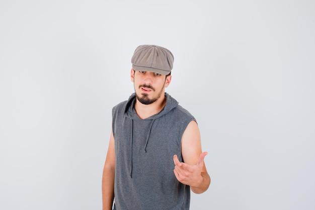 Młody pracownik stoi prosto i wyciąga rękę do przodu w szarej koszulce i czapce i wygląda na szczęśliwego