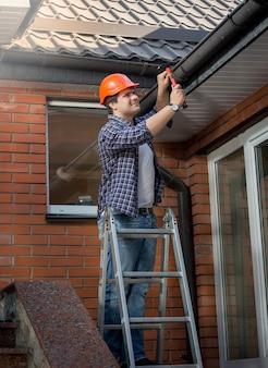 Młody pracownik stojący na drabinie i naprawiający rynnę w domu