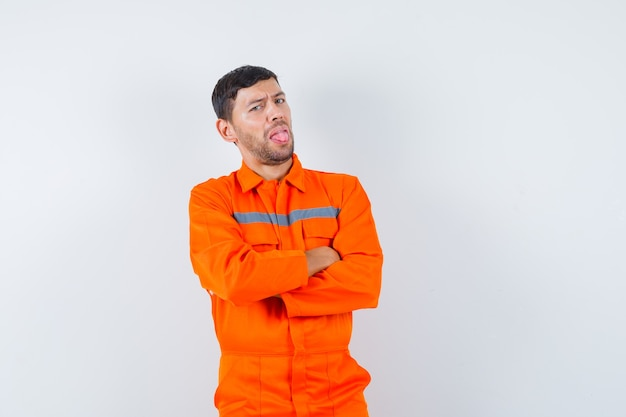Młody pracownik stojący ze skrzyżowanymi rękami, wystawiający język w mundurze i wyglądający na niezadowolonego.