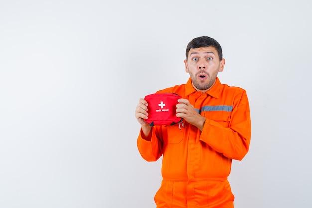 Młody pracownik trzyma apteczkę w mundurze i wygląda zdziwiony.