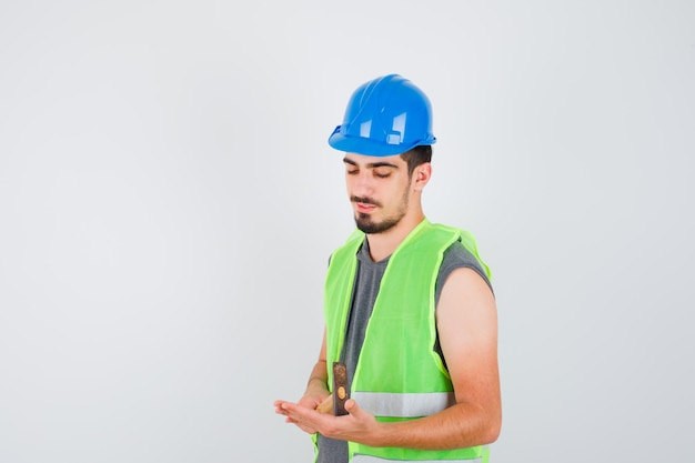 Młody pracownik trzyma siekierę w mundurze budowlanym i wygląda na szczęśliwego