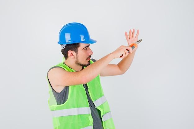 Młody pracownik trzyma szczypce i wyciąga rękę w mundurze budowlanym i wygląda na skupionego