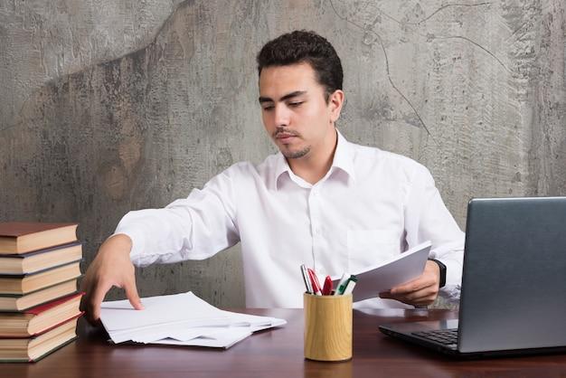 Młody pracownik trzymając arkusze papieru i siedząc przy biurku. wysokiej jakości zdjęcie