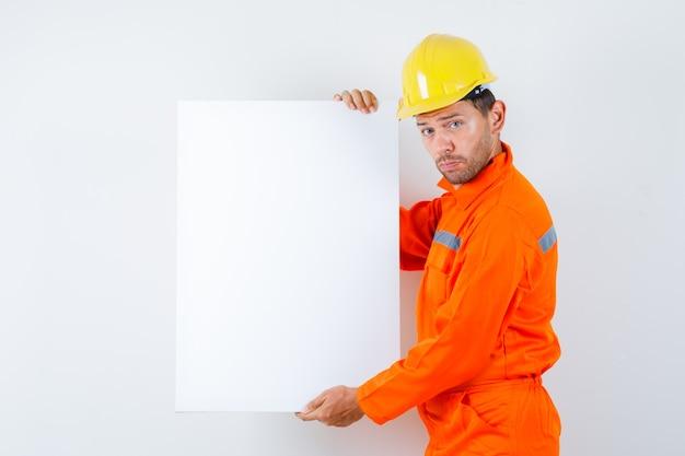 Młody pracownik trzymając puste płótno w mundurze, kask.