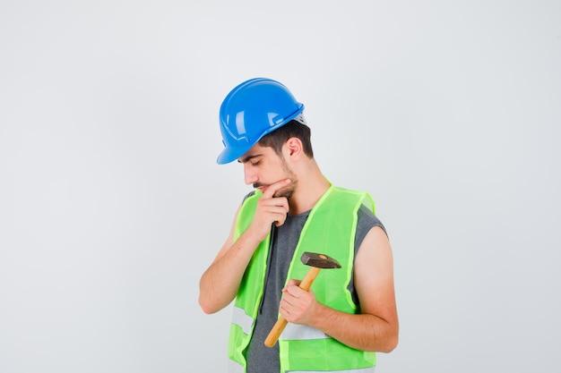 Młody pracownik trzymający siekierę w jednej ręce i stojący w myślącej pozie w mundurze budowlanym i patrzący zamyślony