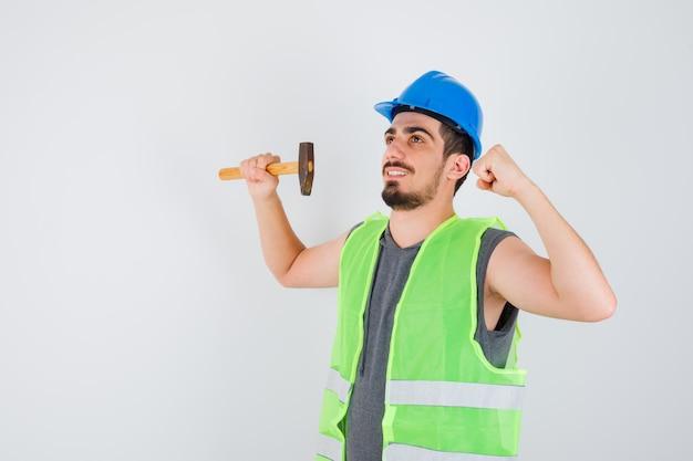 Młody pracownik trzymający siekierę w jednej ręce, pokazując gest mocy w mundurze budowlanym i wyglądający na szczęśliwego