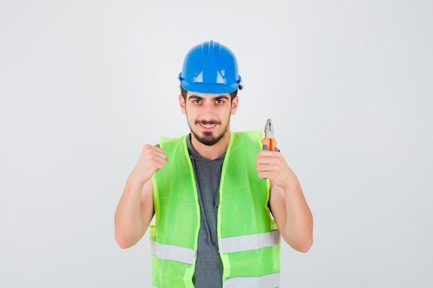 Młody pracownik trzymający szczypce i zaciskającą pięść w mundurze budowlanym i wyglądający na szczęśliwego