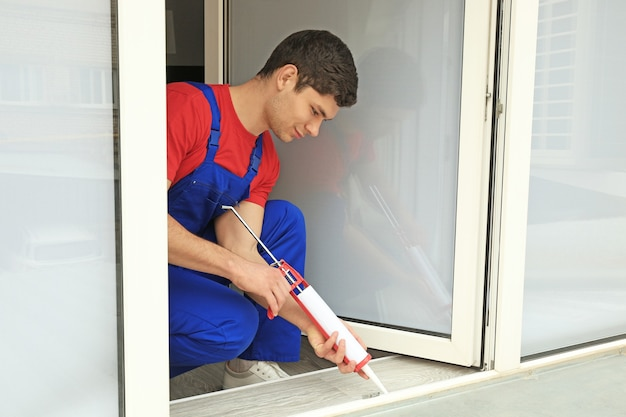 Młody pracownik uszczelniający złącza okna w biurze