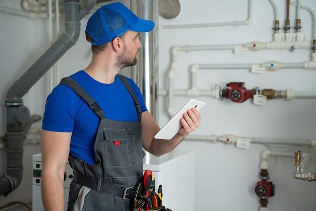 Młody pracownik w kombinezonie ochronnym używa tabletu podczas sprawdzania wyposażenia kotła w domu