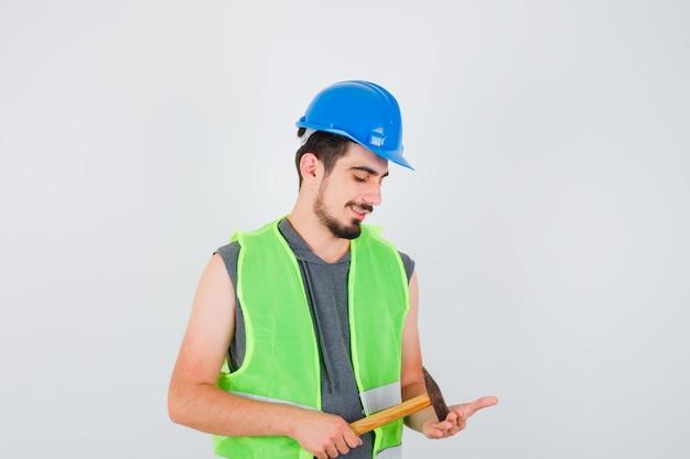 Młody pracownik w mundurze budowlanym trzyma siekierę i wygląda na szczęśliwego