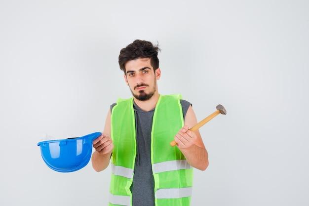 Młody pracownik w mundurze budowlanym trzyma siekierę w jednej ręce, a czapkę w drugiej i wygląda poważnie