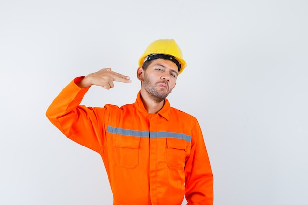 Młody pracownik w mundurze gestykuluje ręką i palcami i wygląda pewnie.