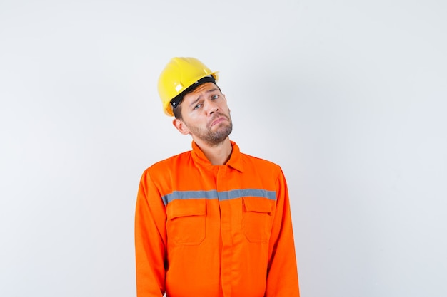 Młody pracownik w mundurze patrząc z przodu i wyglądający na pokornego.