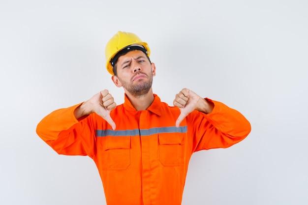 Młody pracownik w mundurze pokazuje podwójny kciuk w dół i wygląda na rozczarowanego.