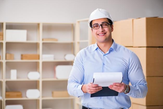 Młody pracownik w urzędzie pocztowym zajmujący się paczkami