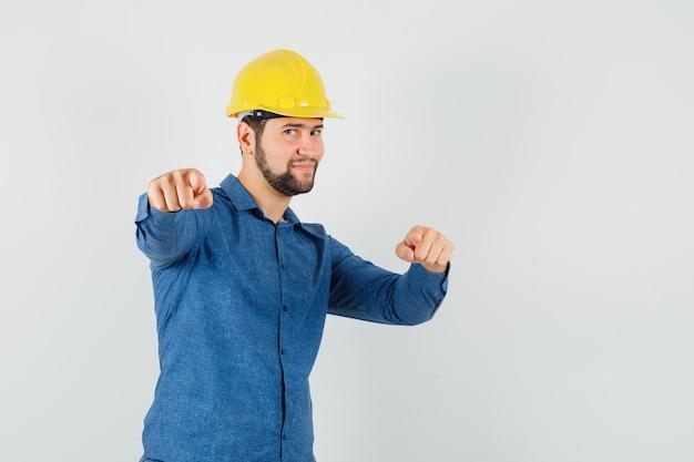 Młody pracownik, wskazując na aparat w koszuli, kasku i patrząc optymistycznie.