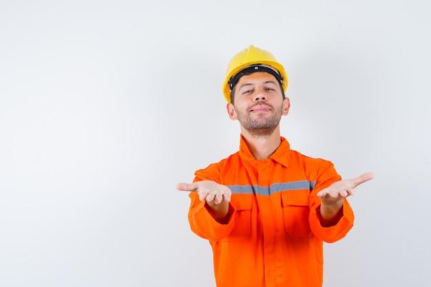 Młody pracownik wyciągający ręce, oferujący coś w mundurze, kasku i wyglądający wesoło.