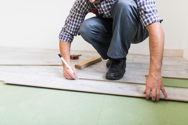 Młody pracownik wykłada podłogę laminowanymi deskami podłogowymi