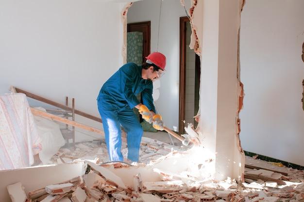 Młody pracownik z czerwonym kaskiem ochronnym i ubrany w niebieski kombinezon kocioł. koncepcja rozbiórki