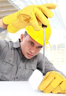 Młody pracownik z żółtym hardhat