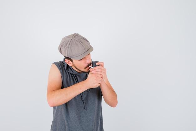 Młody pracownik zapala papierosa w szarej koszulce i czapce i wygląda poważnie