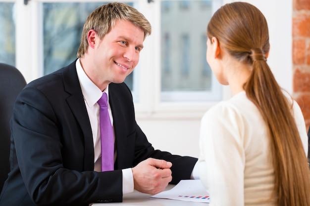 Młody prawnik, agent ubezpieczeniowy lub adwokat pracujący w jego biurze i odbywający konsultacje z klientką lub klientką