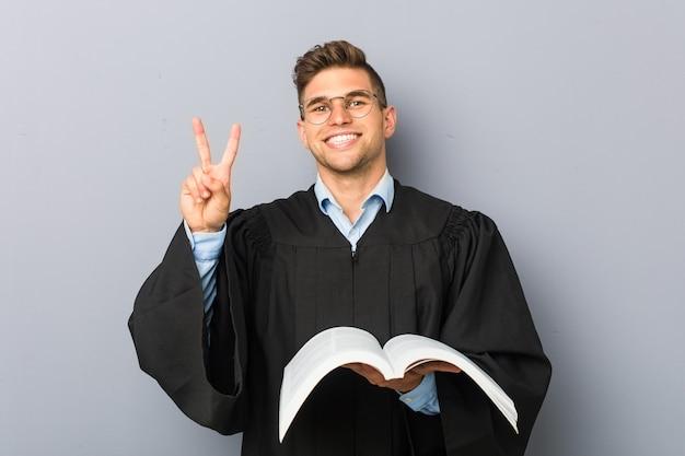 Młody prawnik trzyma książkę pokazującą numer dwa palcami.