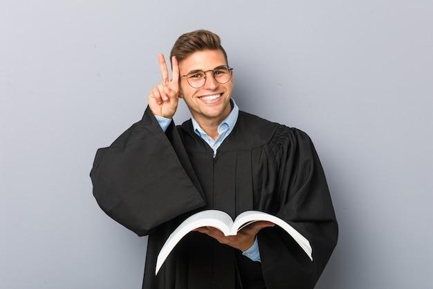 Młody prawnik trzyma książkę przedstawiającą znak zwycięstwa i szeroko się uśmiecha.