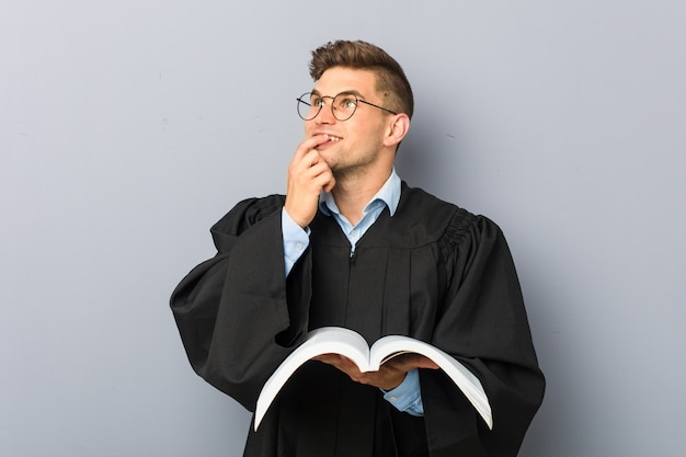Młody prawnik trzyma książkę relaksował główkowanie o coś patrzeje odbitkową przestrzeń.