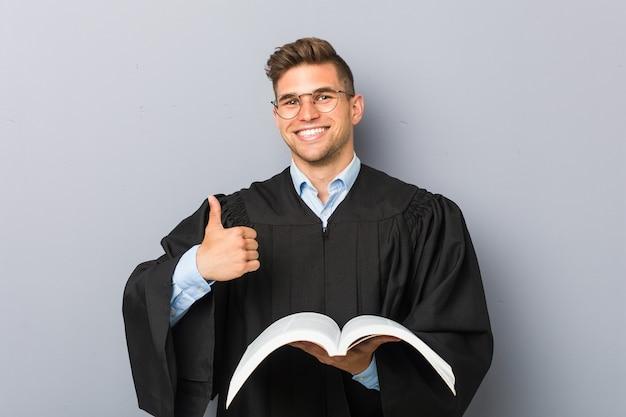 Młody prawnik trzyma książkę, uśmiechając się i podnosząc kciuk do góry