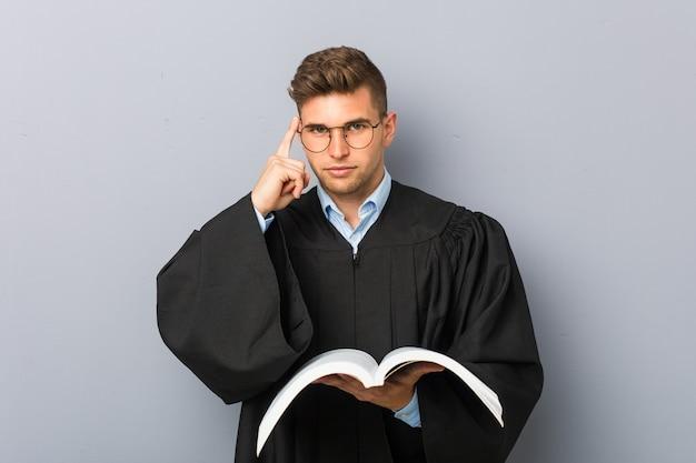 Młody prawnik trzymający książkę, wskazując palcem na skroń, myśląc, skupiony na zadaniu.