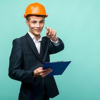 Młody profesjonalista ubrany w twardy kapelusz i niosący punkt schowka w aparacie na niebieskim tle