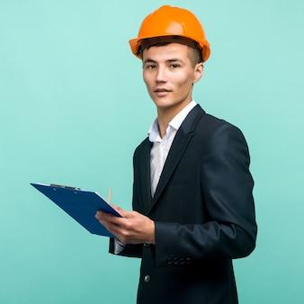 Młody profesjonalista ubrany w twardy kapelusz i niosący schowek na niebieskim tle