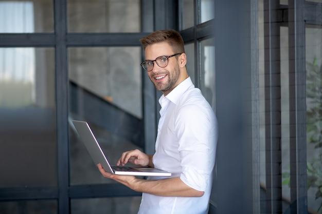 Młody profesjonalista. uśmiechnięty, oficjalnie ubrany mężczyzna pracujący z komputerem