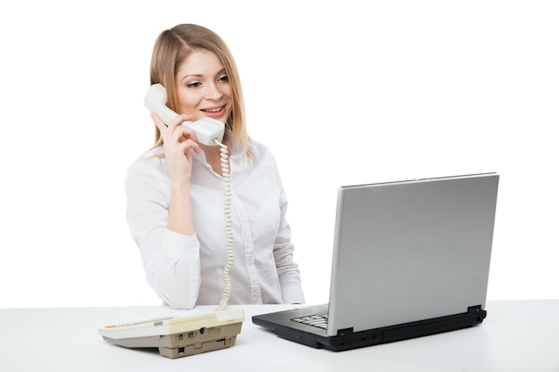 Młody profesjonalny biznes kobieta pracuje przy biurku z laptopem i uśmiechając się podczas rozmowy telefonicznej i rozmowy telefonicznej na białym tle.