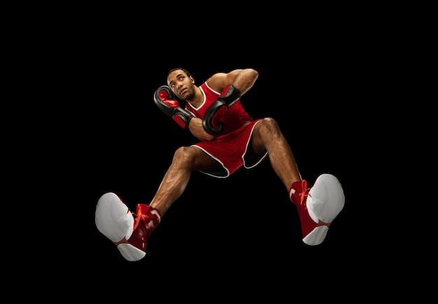 Młody profesjonalny bokser afro-amerykański w akcji, ruch na białym tle na czarnej ścianie, spojrzenie od dołu. pojęcie sportu, ruchu, energii i dynamicznego, zdrowego stylu życia. trening, ćwiczenie.
