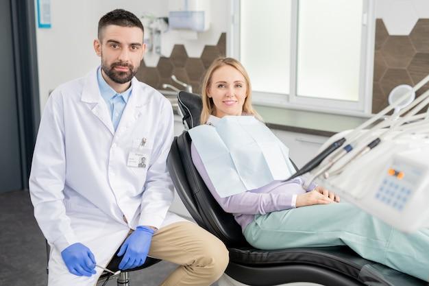 Młody profesjonalny dentysta w rękawiczkach i białym fartuchu i jego blond pacjentka ze zdrowym uśmiechem patrząc na ciebie