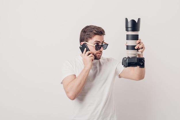 Młody profesjonalny fotograf w białej koszuli trzyma ciężki aparat cyfrowy z długim obiektywem i rozmawia przez telefon z klientem. miękkie światło