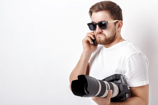 Młody profesjonalny fotograf w białej koszuli trzyma ciężki aparat cyfrowy z długim obiektywem i rozmawia przez telefon z klientem