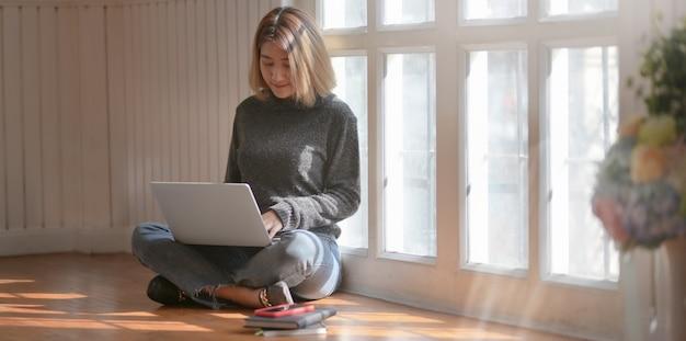Młody profesjonalny freelancer pracujący nad swoim projektem, siedząc w pobliżu okien