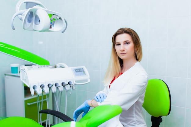Młody profesjonalny lekarz dentysta w nowoczesnym gabinecie ze sprzętem stomatologicznym. pojęcie ubezpieczenia zdrowotnego i bezpłatnej opieki stomatologicznej. protetyka i montaż licówek.