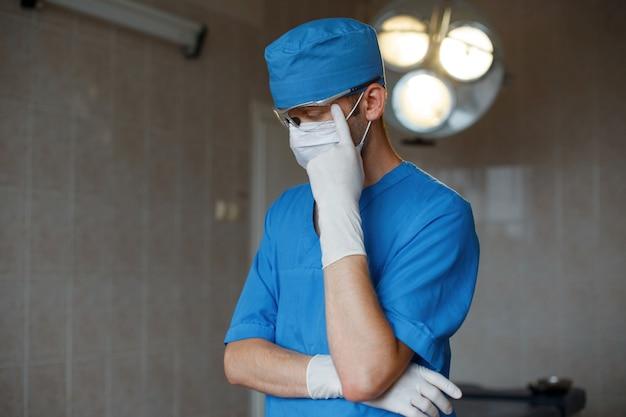 Młody profesjonalny lekarz w niebieskim mundurze w okularach z rękawiczkami w masce myśli na sali operacyjnej