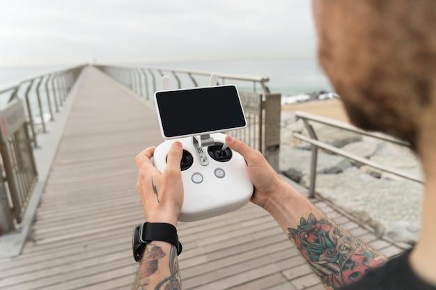 Młody profesjonalny lub amator fotograf lub pilot drona trzyma panel zdalnego sterowania z ekranem i elementami sterującymi gotowymi do lotu dronem w powietrzu, aby zobaczyć ptasi punkt widzenia.