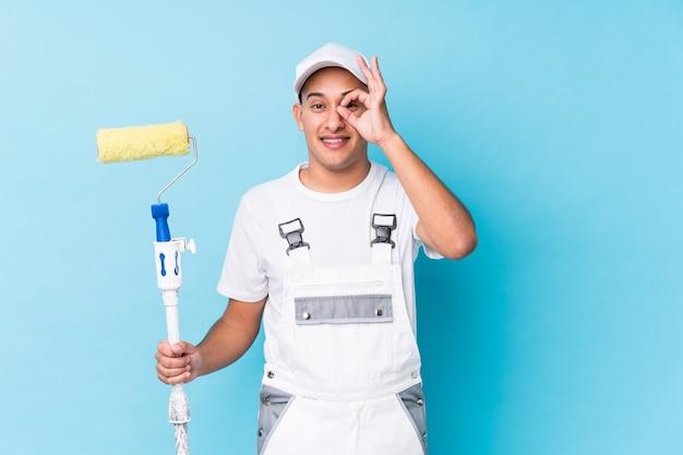 Młody profesjonalny malarz łaciński mężczyzna na białym tle podekscytowany utrzymując ok gest na oko.