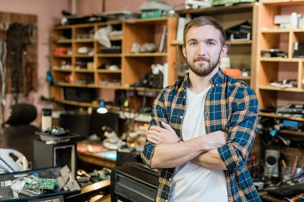 Młody profesjonalny mechanik zepsutych gadżetów krzyżujący ramiona przy klatce piersiowej, stojąc przed kamerą w swoim warsztacie