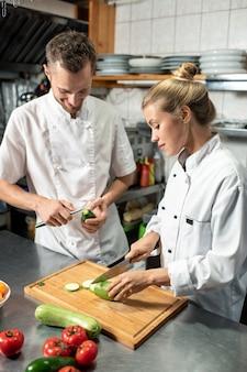 Młody profesjonalny męski szef kuchni z nożem obierającym awokado, podczas gdy jego żeńska praktykantka kroi świeżą cukinię na drewnianej desce w kuchni