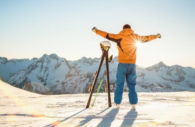 Młody profesjonalny narciarz o zachodzie słońca na chwilę relaksu w ośrodku narciarskim w francuskich alpach