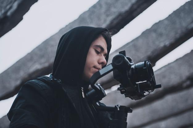 Młody profesjonalny operator kręci w opuszczonym budynku, jesienna praca ekipy filmowej. widok z ziemi